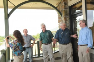 Casey Crocker, photographer with Arkansas Parks and Tourism; Greg Butts, Director of Arkansas State Parks; Richard Davies, Executive Director of Arkansas Parks and Tourism, and Gar Eisele of Mena enjoy the new porch at Queen Wilhelmina State Park during a news conference June 11, 2015. Photo by Z. Clift