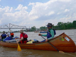 John Ruskey paddling his voyager canoe with the Helena Bridge in the background. Photo by Z. Clift